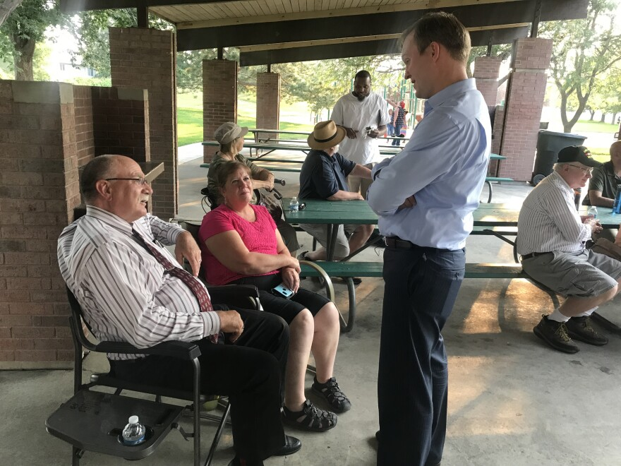 Ben McAdams speaks with a couple in the park.