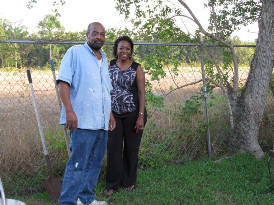 Anthony and Eunice Crane stand in their backyard in Gulfport, Miss. The new port access road will be built behind their fence. Their home used to back to other homes.