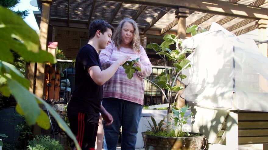 Sarah McKenna and her son, Ian, look at the leaves of a plant in the garden of their home.