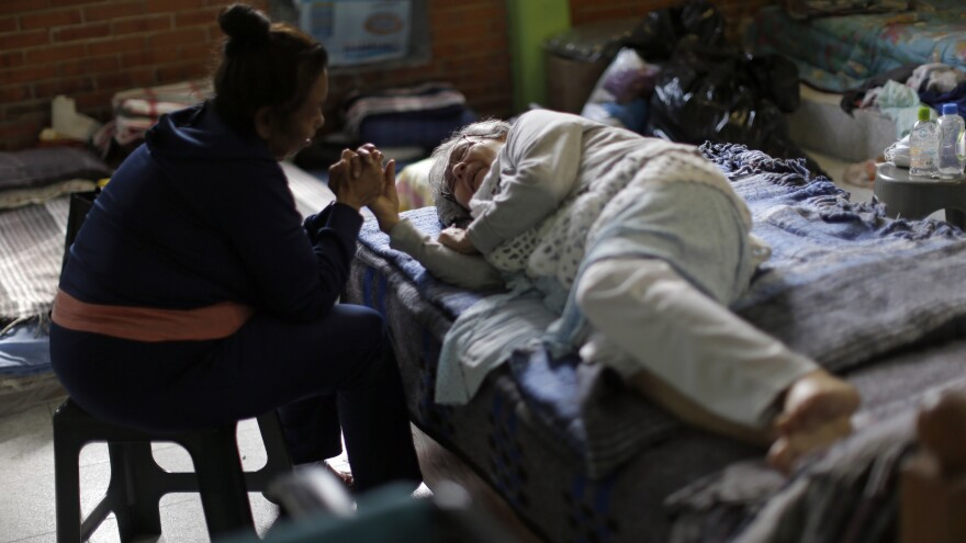 "Maria Antonia Lopez holds the hand of 81-year-old Angelina Usuna Garcia at the Francisco Kino school, which was turned into a temporary shelter for residents who had to evacuate their homes in Mexico City. ""The government has the last word"" about when residents can return to their homes, Usuna told the AP, ""and no one knows anything about the government here."""