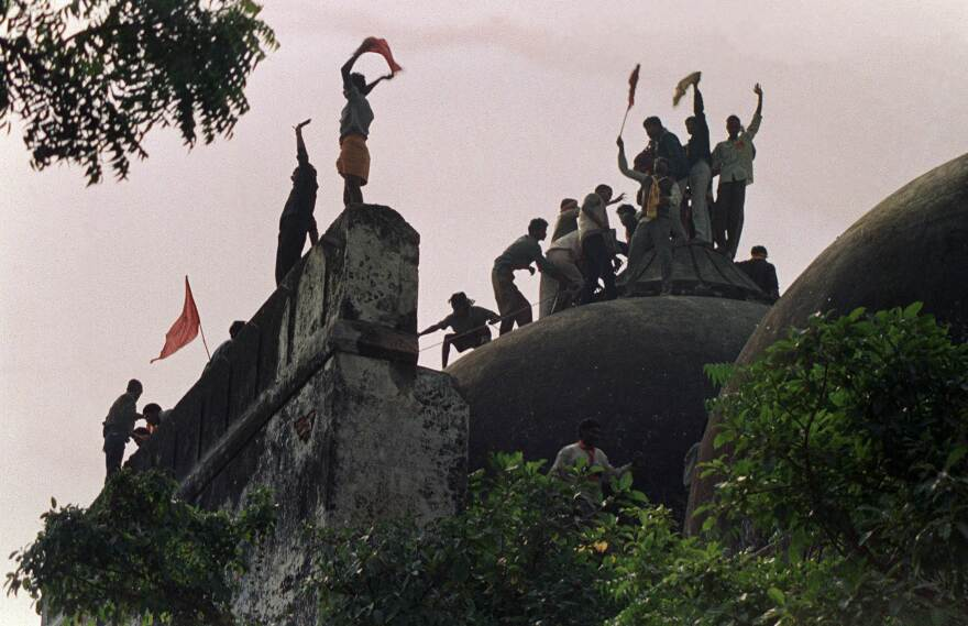 Hindus shout and wave banners on top of a stone wall as they celebrate the destruction of the 16th-century Babri mosque in Ayodhya in December 1992.