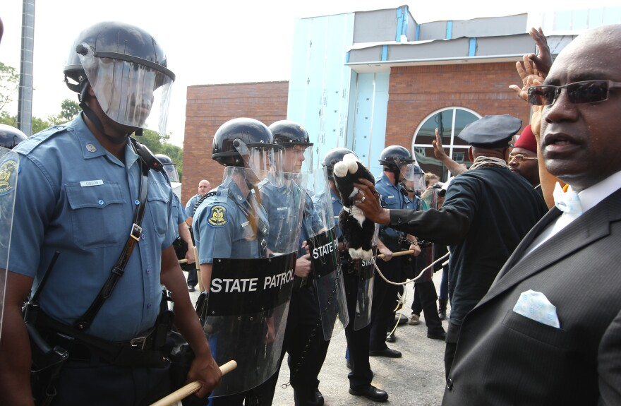 Protesters are greeted by a wall of police officers after a march to the Ferguson Police department on August 11, 2014.