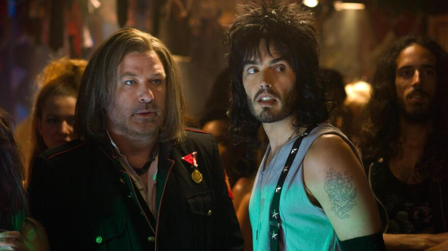 Club owner Dennis Dupree (Alec Baldwin, left) and his assistant Lonny Barnett (Russell Brand) try to figure out a way to keep their nightclub open in the movie adaptation of <em>Rock of Ages</em>.