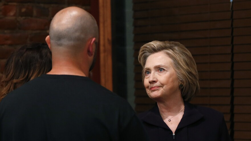 Democratic presidential candidate Hillary Clinton talks with Bo Copley, who recently lost his job at a coal company, at a campaign roundtable in West Virginia on May 2, 2016.