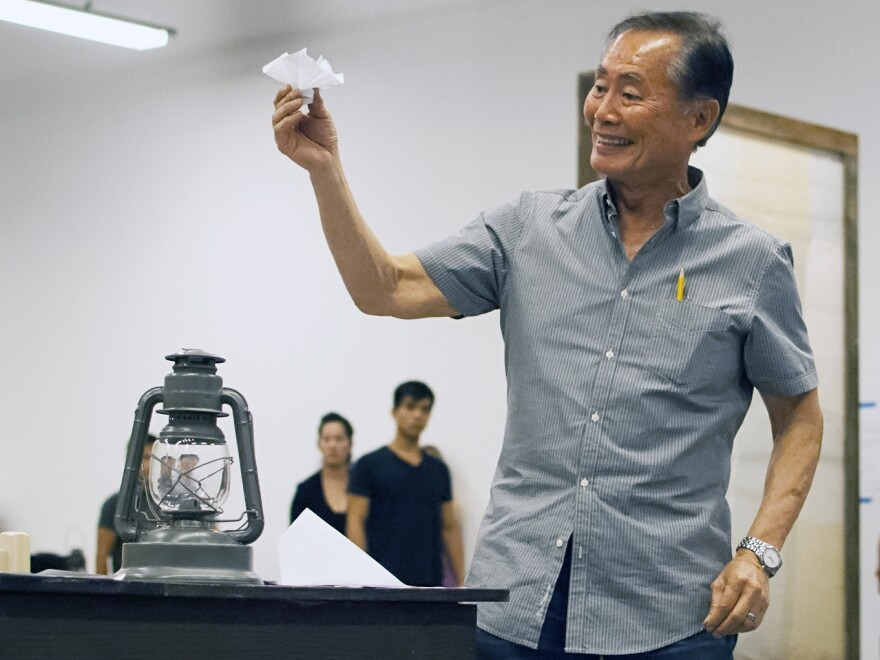 Takei rehearses a scene in which his character, Ojii-San, tries to cheer his granddaughter up by making her an origami flower out of a loyalty questionnaire.