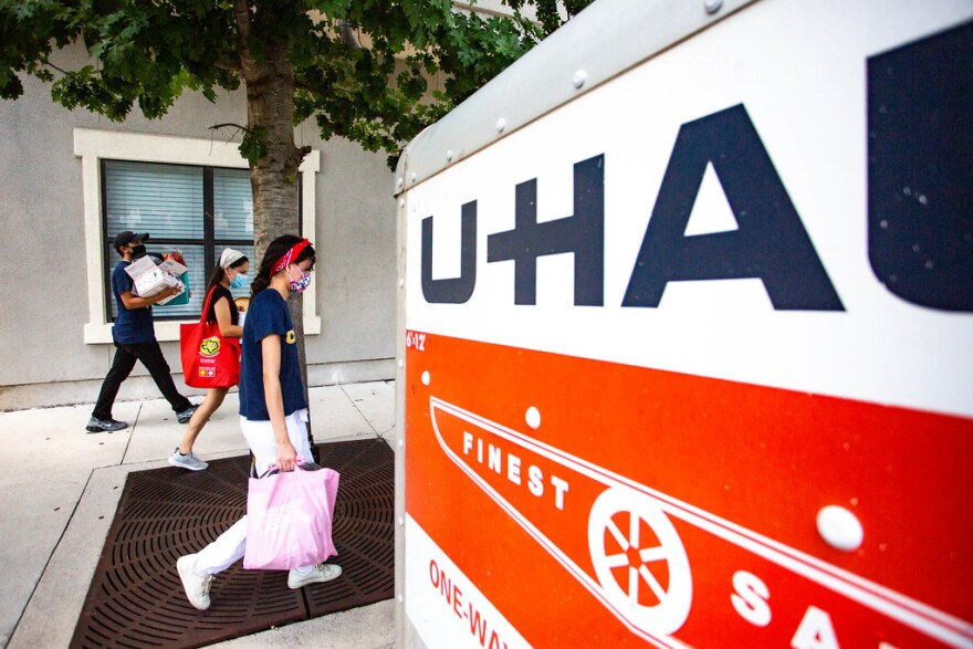 Sisters Danielle and Kimberly Medina pack a U-Haul to move to a new apartment on West Campus before the start of UT's fall semester.