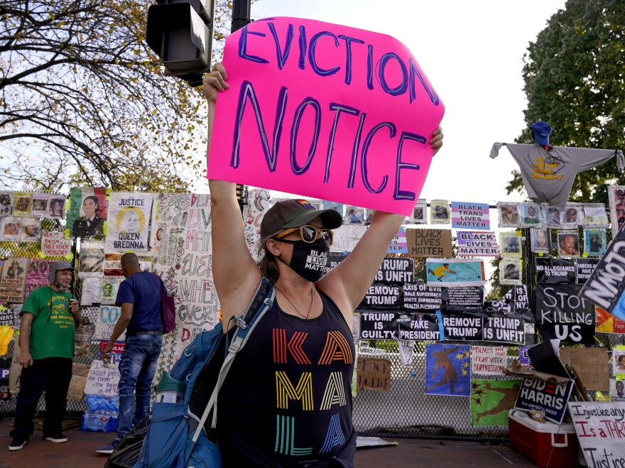 A protestor holds up an eviction sign in Washington, DC. The rescue package just passed in Congress sets aside $25 billion for rental assistance and extends a CDC order aimed at preventing evictions.