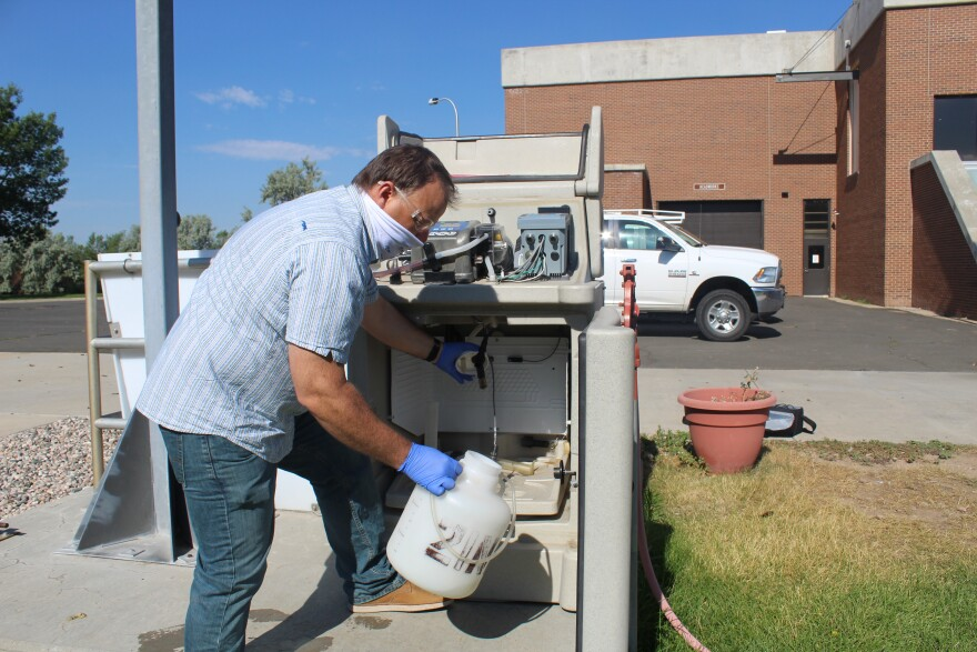 Jason Graham, director of wastewater plant operations with the city of Fort Collins, pulls a plastic jug from a sampling machine at the Drake Water Reclamation facility.