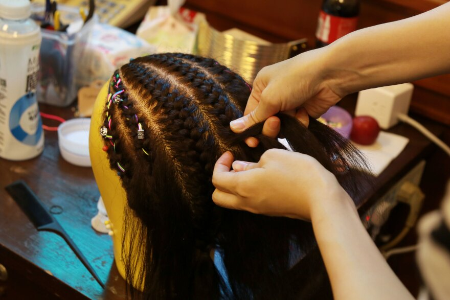 The production's costume designer braids a wig.