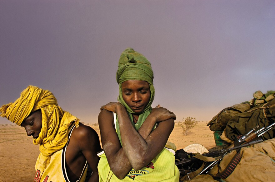Soldiers with the Sudanese People's Liberation Army sit by their truck, waiting for it to be repaired, as a sandstorm approaches in Darfur. August 2004