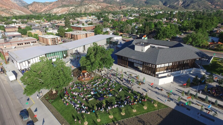An aerial shot shows an audience seated on a lawn watching an outdoor stage
