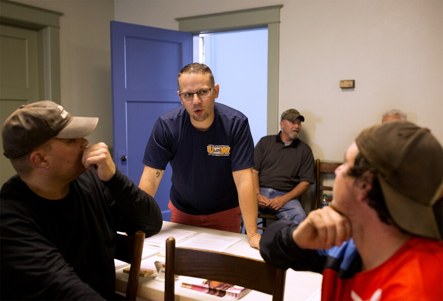 Jason Fernandez speaks with union members before the start of a meeting. May 2018
