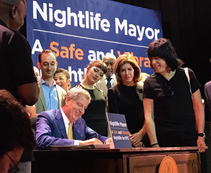 New York City Mayor Bill de Blasio signs a bill establishing the Office of Nightlife at the House of Yes in Bushwick, Brooklyn. Right, Marky Ramone.