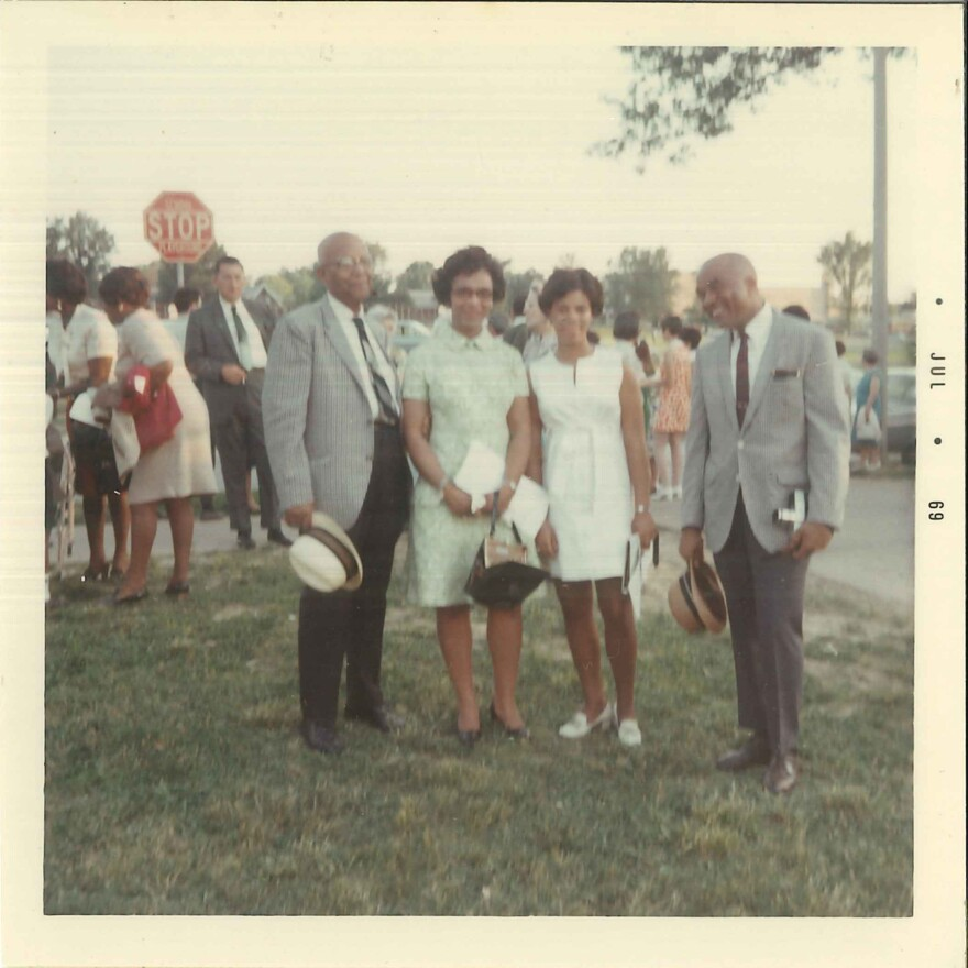 Judy Gladney (in white) poses on her graduation day with her grandfather (at left) and her parents, Dr. John and Clarice Gladney.