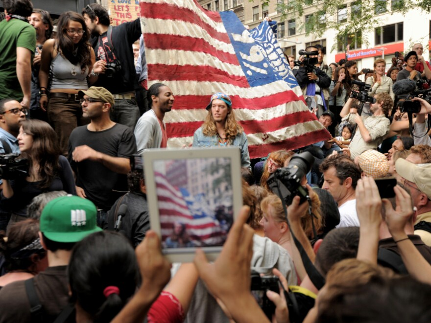 <p>An onlooker takes a photograph of Occupy Wall Street protesters in New York's Zuccotti Park. The demonstrations were inspired by a blog post by Kalle Lasn, founder of <em>Adbusters</em> magazine.</p>