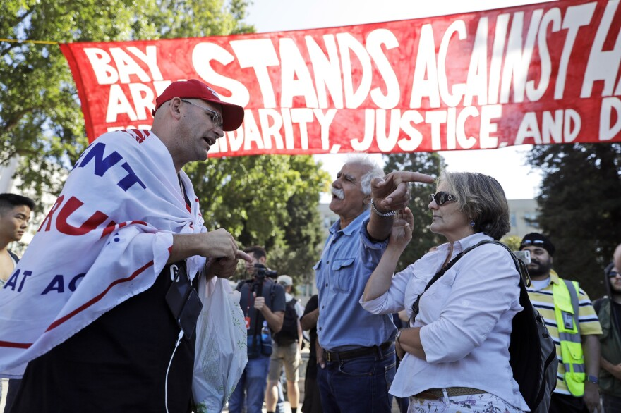 """Donald Trump supporter Arthur Schaper, left, argues his position with Mustafa Payrvand, center, and Christina Tunnah during a free speech rally Sunday, Aug. 27, 2017, in Berkeley, Calif. Protesters gathered for a """"Rally Against Hate"""" in response to a planned right-wing protest that raised concerns of clashes and prompted a large police presence. (AP Photo/Marcio Jose Sanchez)"""