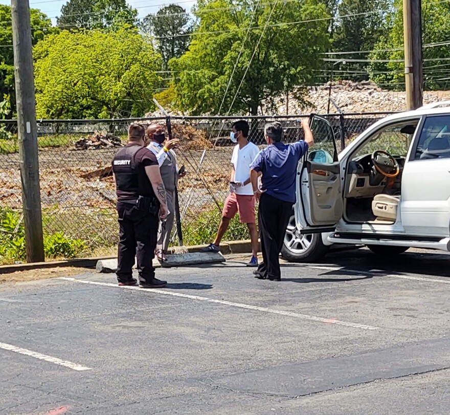 Sheriff Garry McFadden (second from left) talked with the Days Inn manager (third from left) as a security guard and an unidentified man looked on Tuesday.