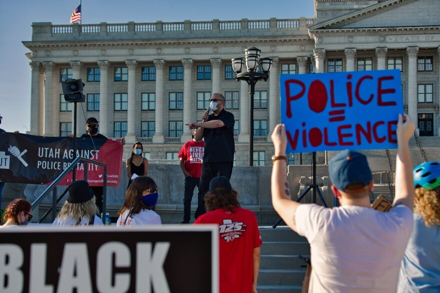 "A man in a black shirt and a white mask speaks to a group of people with signs including one that read  ""Police = Violence."""