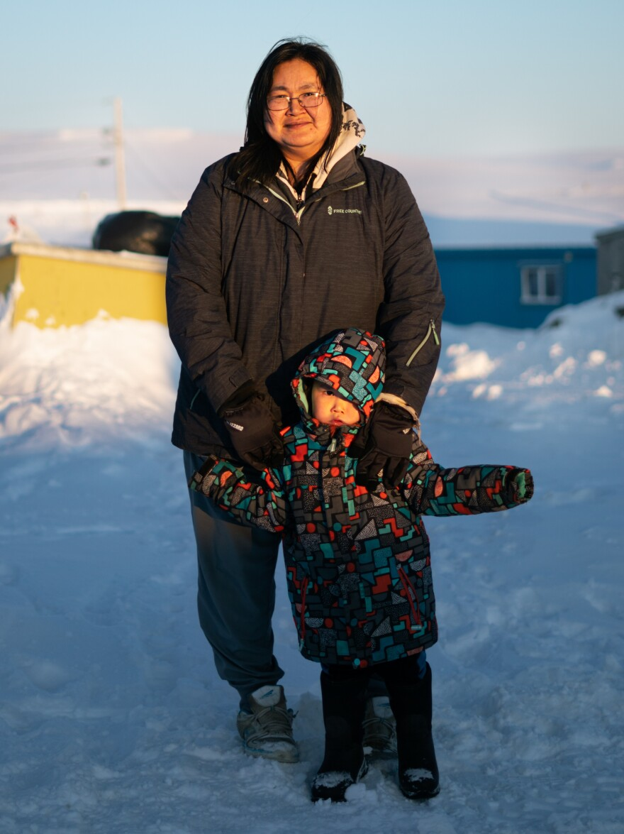 Maria White and her son Lance Jimmie, 3, stand near their home in Toksook Bay. White works at Bayview General Merchandise, one of the three convenience stores in Toksook Bay.
