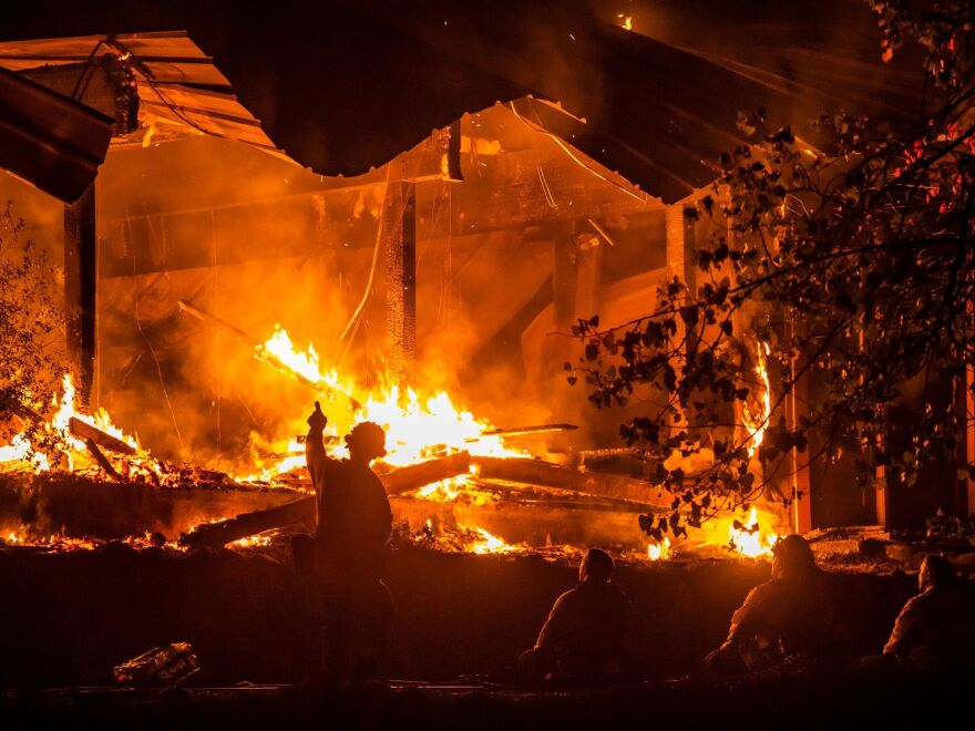 Firefighters look on as a structure burns during the Kincade Fire off Highway 128, east of Healdsburg, Calif., on Tuesday.