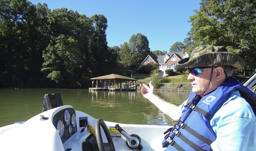 Charlie McRorie steers his boat on Brown's Cove, off Lake Wylie. A major coal ash spill at the nearby Allen plant  would affect his dock and yard (background).