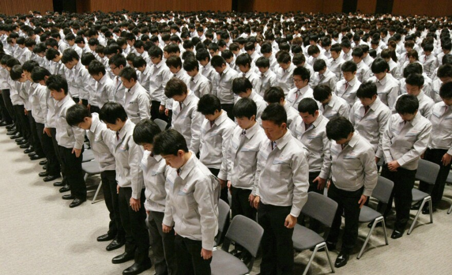 Newly recruited Toyota Motor employees bow their heads in prayer for disaster victims at a ceremony in Toyota City in Aichi prefecture on April 1.