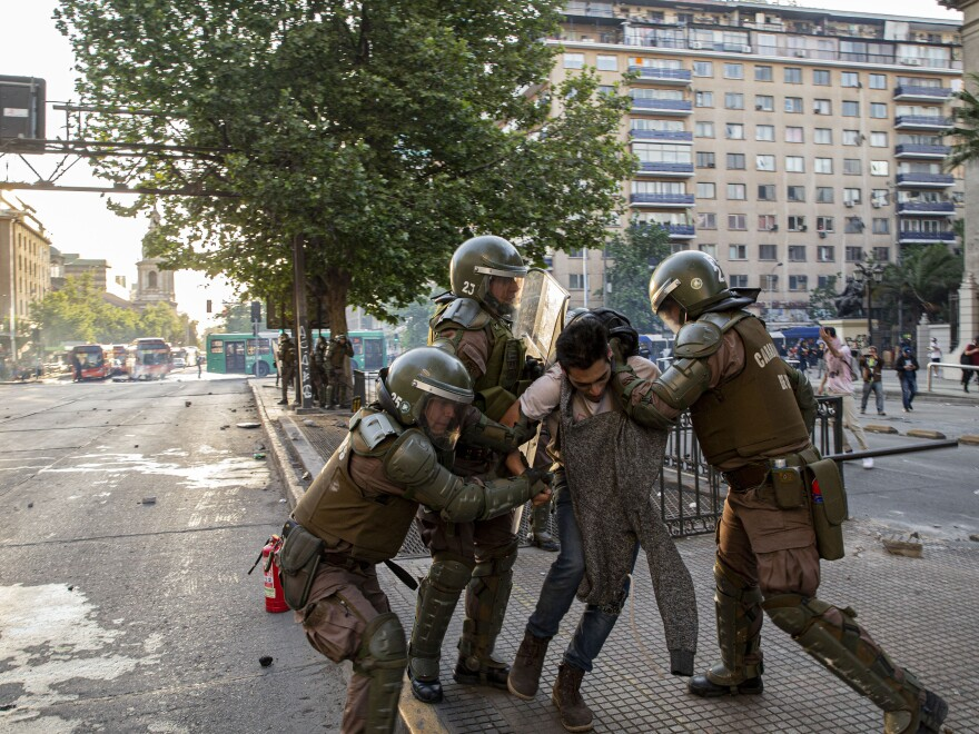Chilean police detain a man during a protest; law enforcement met with some violent resistance when trying to clear subway stations.