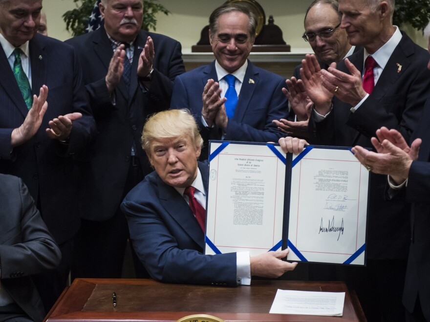 President Trump shows off the Veterans Choice Program Extension and Improvement Act after signing it in April 2017. A new report said on Thursday that the agency failed in its core mission of protecting whistleblowers.