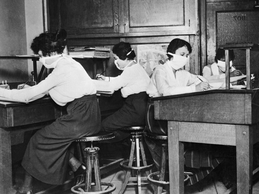 They had the right idea: During the worldwide flu epidemic that began in 1918, women in this U.S. office wore cloth masks.
