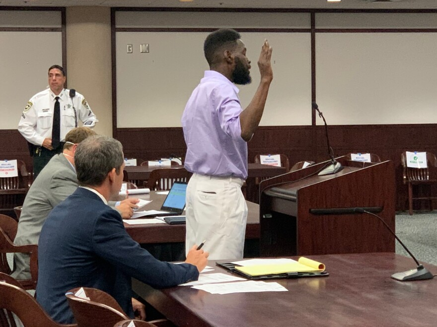 man at courtroom podium takes oath