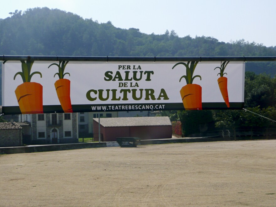 """Banners at the entrance to the village of Bescanó announce the local theater's carrot-selling campaign, with the slogan """"For the Health of Culture,"""" in Catalan language."""