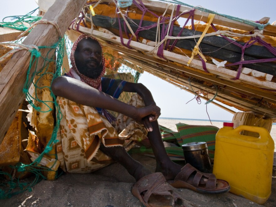 Suleman Ahmen Aden shades himself beneath his fishing raft. Last year, he helped  catch pirates who were forced to beach their boat because of a disabled engine.