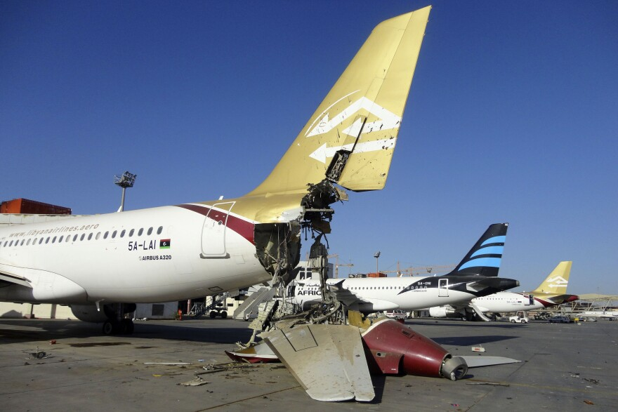 An airplane damaged by shelling at Tripoli International Airport on Saturday. Unidentified warplanes attacked targets in Libya's capital, Tripoli, on Sunday, residents said, hours after forces from the city of Misrata said they had seized the main airport.