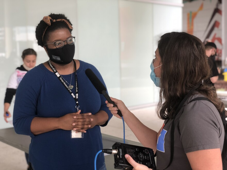 a woman wearing a mask talks into a microphone.