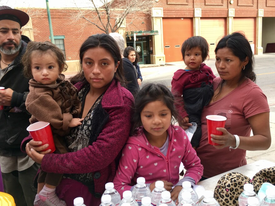 Two Guatemalan mothers released from federal custody get water at a volunteer station in downtown El Paso on Christmas Day.