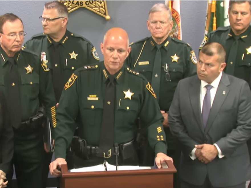 Pinellas County Sheriff Gualtieri pictured standing at a podium surrounded by law enforcement officers.