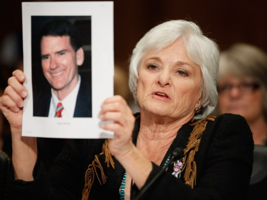 Patricia Maisch, one of the people who helped halt the Tucson shooting that killed six and wounded 13, including Arizona Rep. Gabrielle Giffords, holds up a photograph of victim John Roll, a federal judge, while testifying before a Senate subcommittee on Tuesday. Maisch testified in support of legislation that would strengthen federal power over the states' handling of background checks.