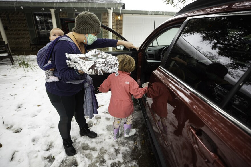 A woman with a baby strapped to her back and a child in front of her puts tinfoil-wrapped food into a car.