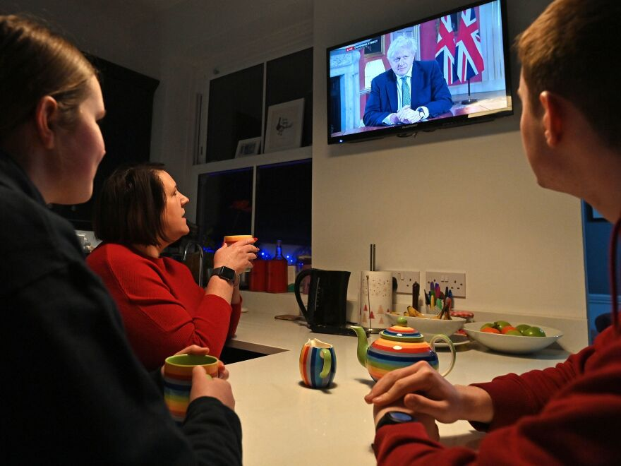 A family gather around the television in Liverpool, England, on Monday to watch Prime Minister Boris Johnson speak to the nation about the new lockdown.