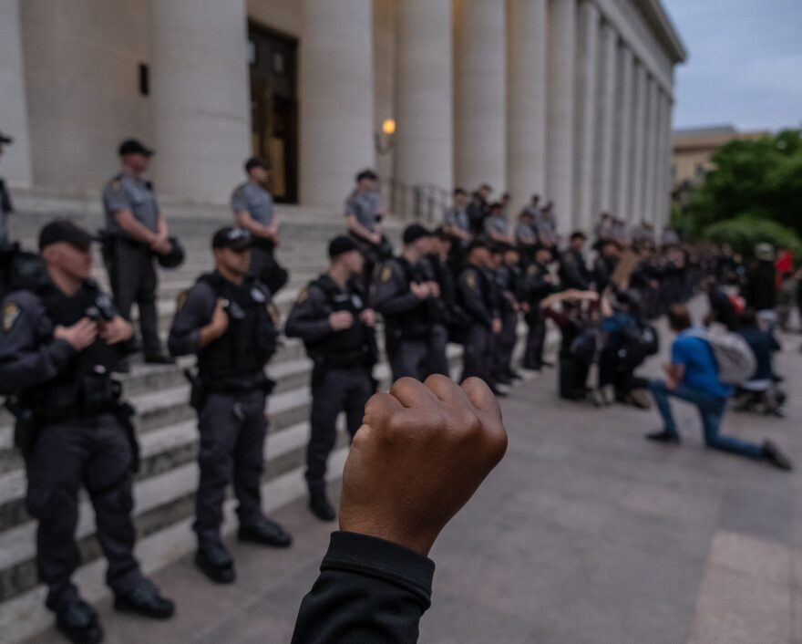 Protesters kneel and raise their arms if front of a row of police officers as they gather peacefully to protest the death of George Floyd at the State Capital building in downtown Columbus, Ohio, on June 1, 2020. (Seth Herald/AFP/Getty Images)
