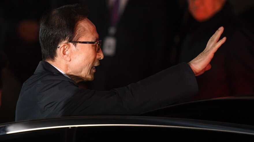 Former South Korean President Lee Myung-Bak waves to the crowd as he is taken into custody outside his residence.