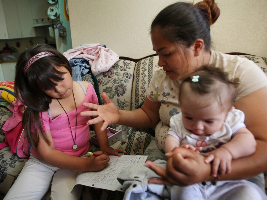In this May 2009 photo, Maya Ramirez, a single mother of five, helps her daughter with homework. Ramirez lives in El Centro Calif., which has one of the highest unemployment rates in the country.