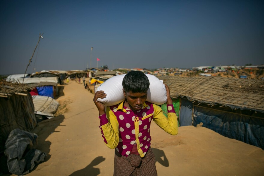 A Rohingya refugee carries a bag of food in the Hakimpara camp in Bangladesh.