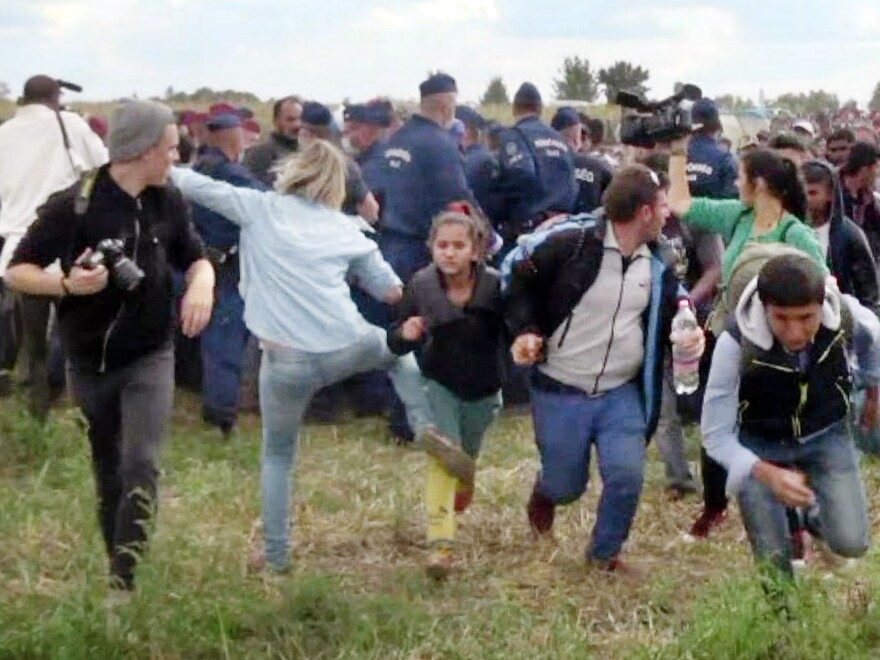 This video grab made on early September shows a Hungarian TV camerawoman kicking a child as she runs with other migrants from a police line during disturbances at Röszke, southern Hungary.