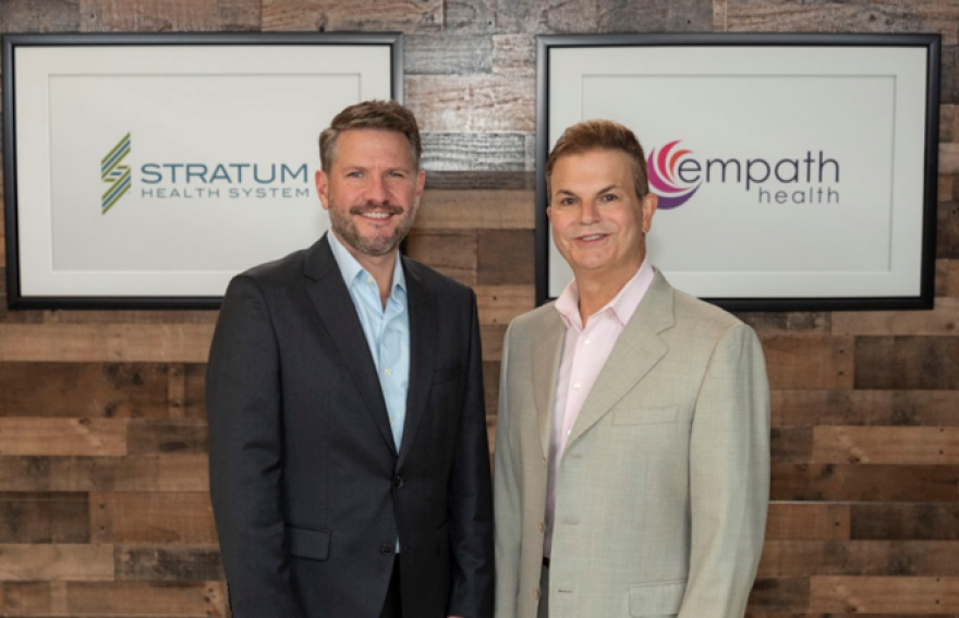Two men, one in a dark blazer and the other in a tan blazer, stand in front of their company signs.