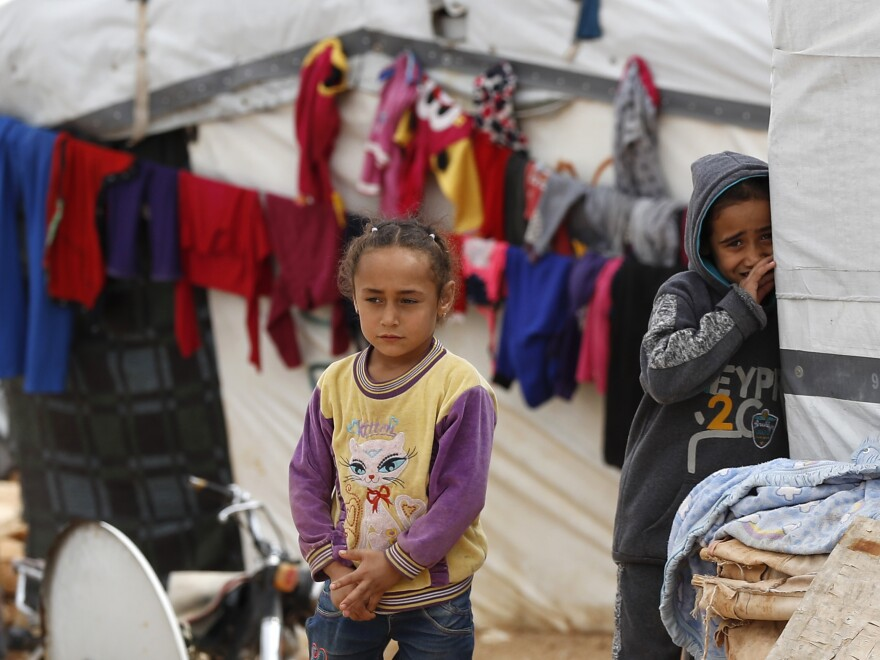 Syrian refugee girls stand outside their tent at a camp near the border with Syria in eastern Lebanon on June 13.