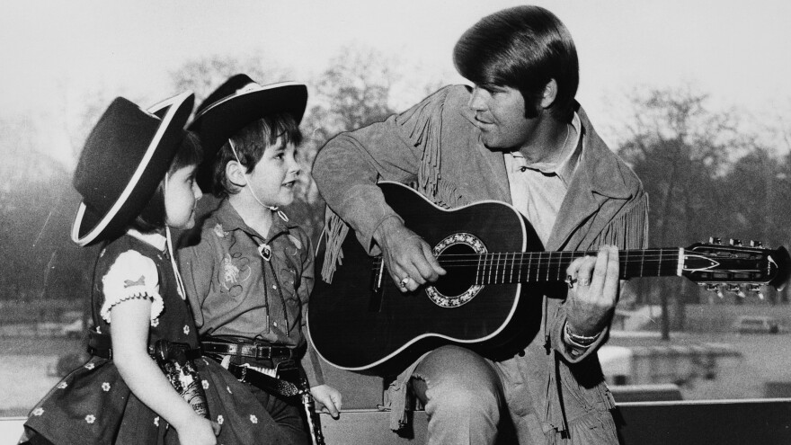 Country singer Glen Campbell playing the guitar for two young fans in 1970.