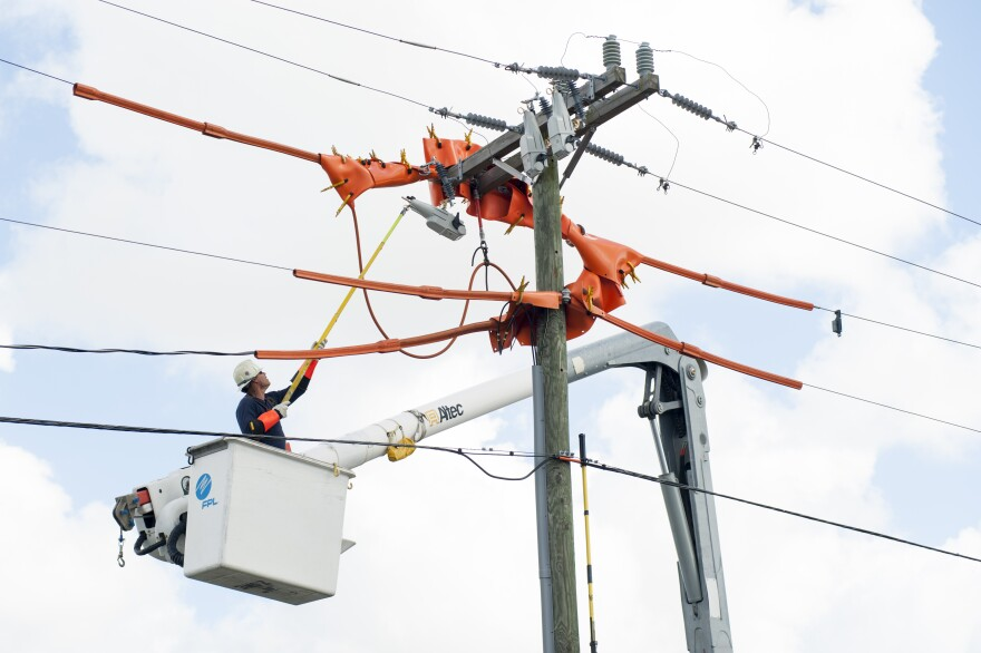 An FPL technician works on a power pole in Miami.