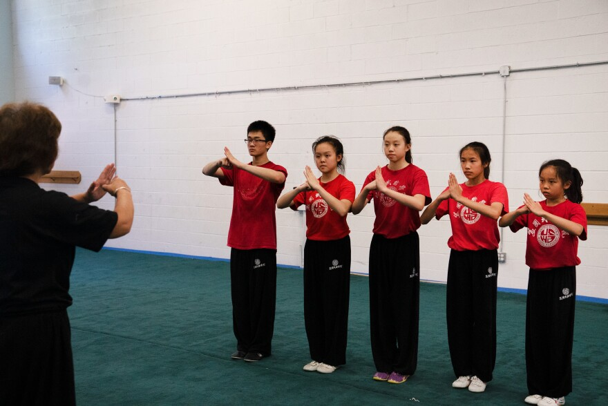 Students greet Zhang before practice. She can be loud and strict, but often call her students Bǎo Bèi Er, or my baby, and  her students call her Mā, or mom.