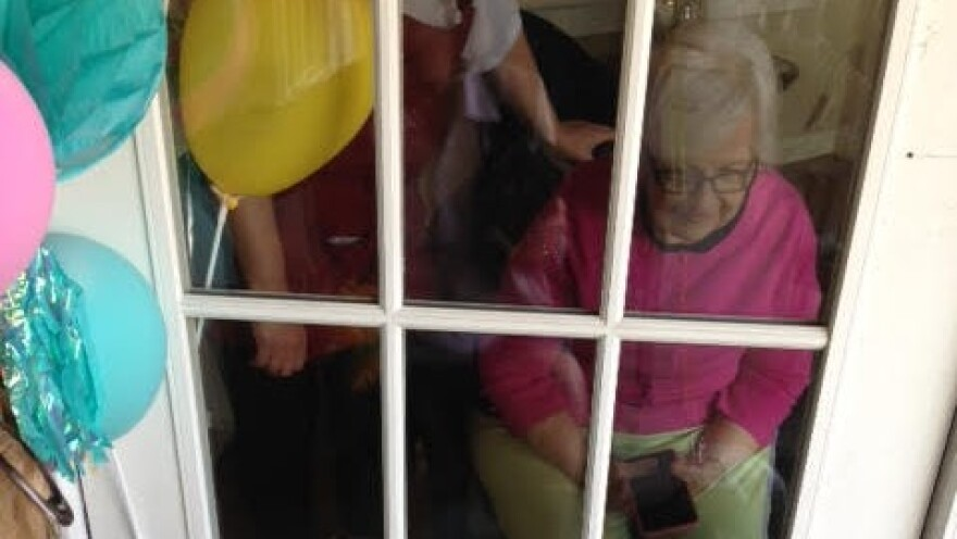 Memory care resident Sue Morse visits through a window with family on Mother's Day 2020 at Sunrise Senior Living in Jacksonville.